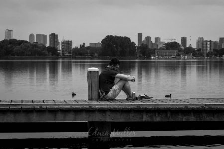 Photo: Edwin MullerStreet photography, man alone in thoughts with city of Rotterdam in background